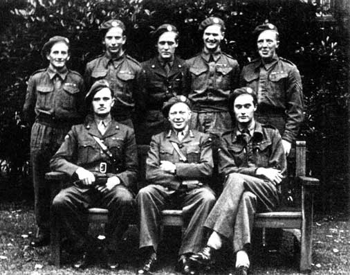 Surrounding their boss Leif Tronstad (front row, center) are most of the Vemork saboteurs, including (front row left to right) Jens Anton Poulsson and Joachim Ronneberg, and (back row left to right) Hans Storhaug, Fredrik Kayser, Kasper Idland, Claus Helberg, and Birger Stromsheim.