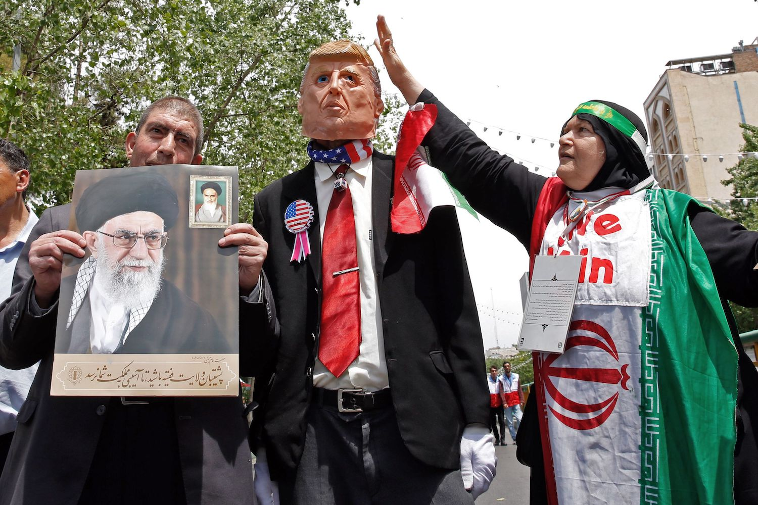 """Iranian demonstrators carry a portrait of Iran's Supreme Leader Ayatollah Ali Khamenei and an effigy of US President Donald Trump during a rally in the capital Tehran, on May 10 2019. - Iranian foreign minister blamed the EU for the decline of Tehran's nuclear accord with world powers and insisted the bloc """"should uphold"""" its obligations under the pact in which Iran agreed to curb its nuclear ambitions in return for sanctions relief. US President Donald Trump pulled the United States out of the agreement in May of last year and reinstated unilateral economic sanctions. (Photo by STR / AFP)        (Photo credit should read STR/AFP/Getty Images)"""
